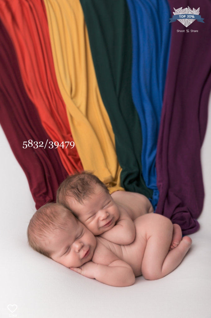 twin babies with rainbow cloths behind them