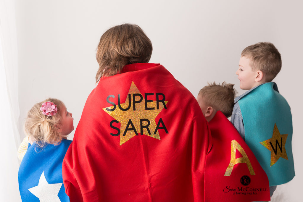 sara mcconnell wearing a cape with three children who are also in capes during their snuggle session photos