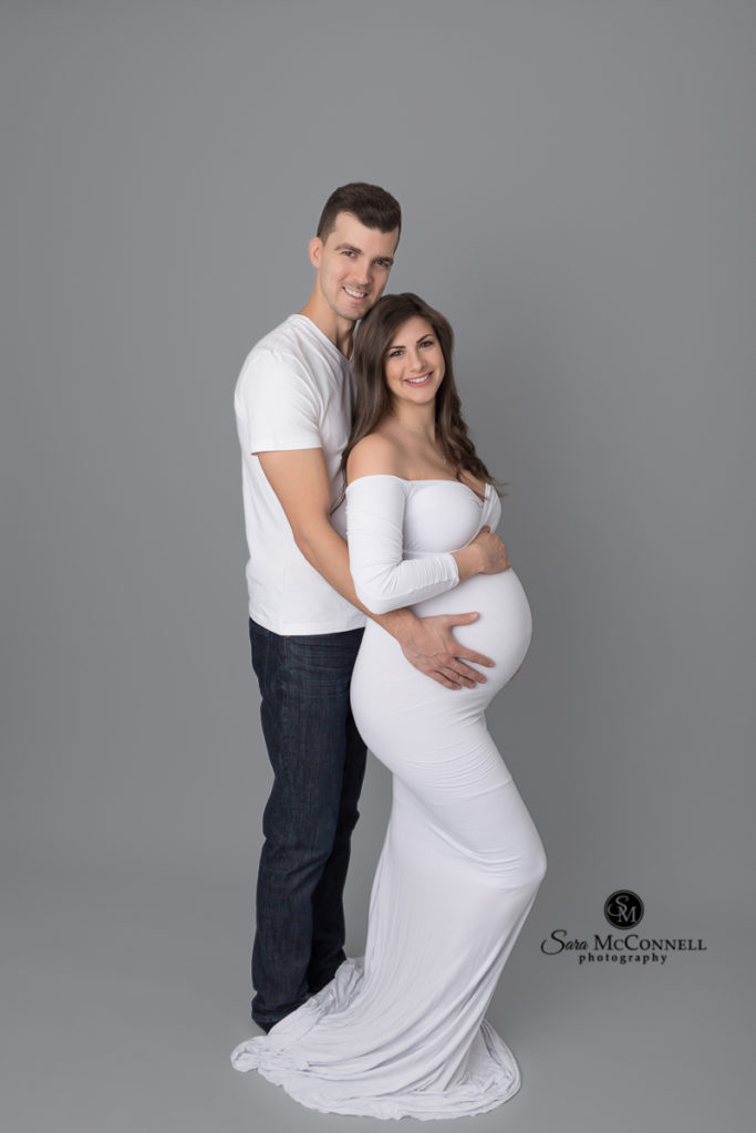 pregnant woman wearing a white gown for her maternity photos
