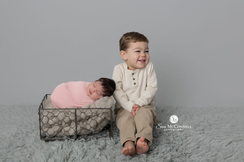 baby wrapped in pink in a wire basket while brother sits beside her