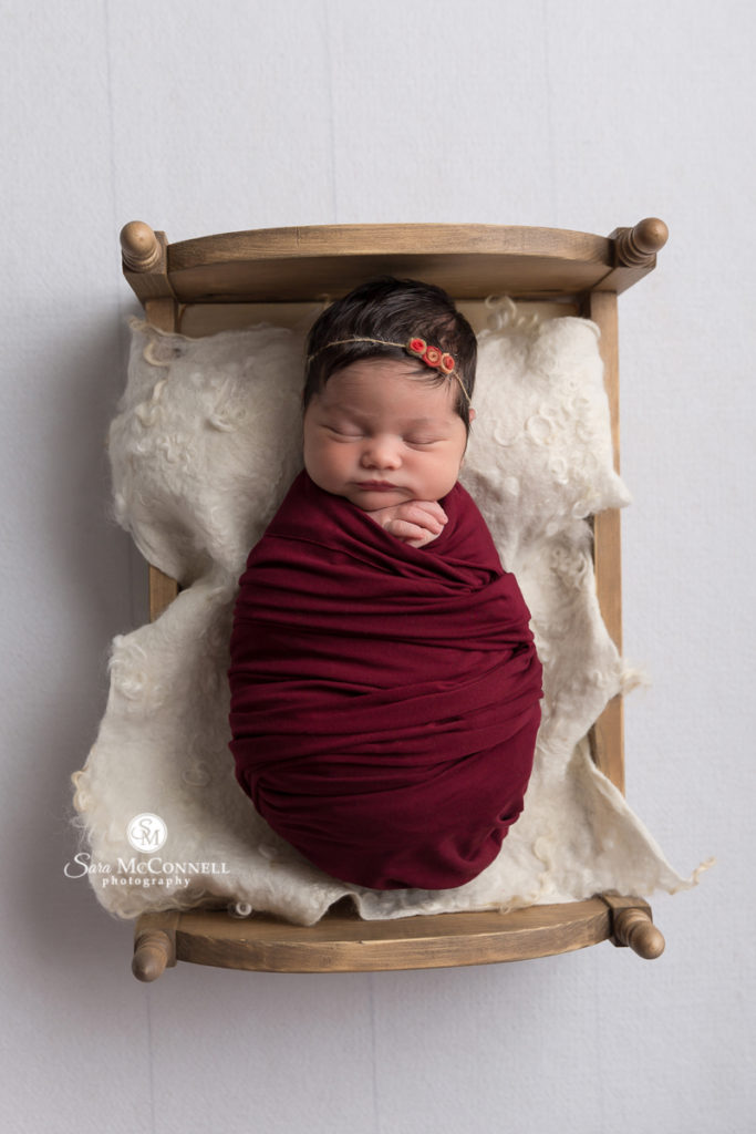 sleeping baby wrapped in burgundy on a wooden bed