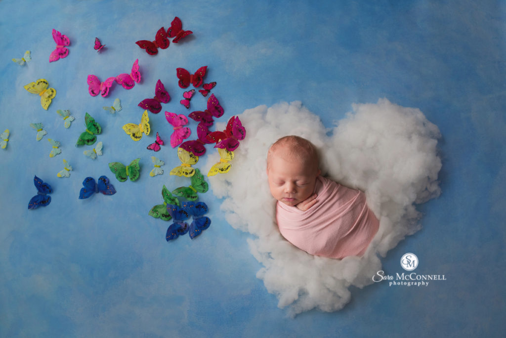 newborn baby sleeping on a heart shape cloud with butterflies