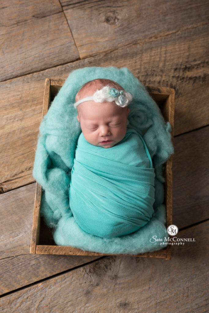 newborn baby wrapped in teal
