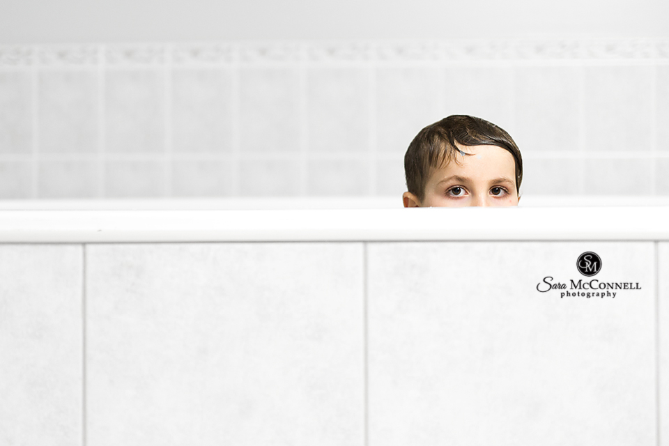 boy peeking out over bath tub
