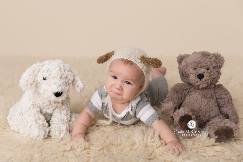 baby wearing crochet puppy ears with stuffed animals