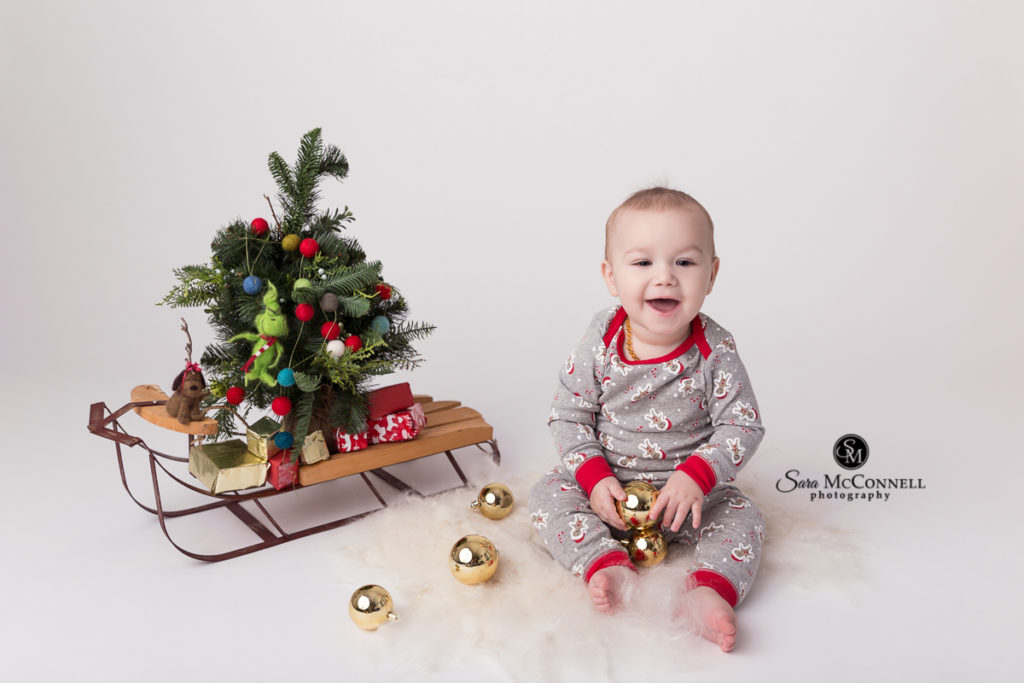 baby beside a christmas tree on a sled