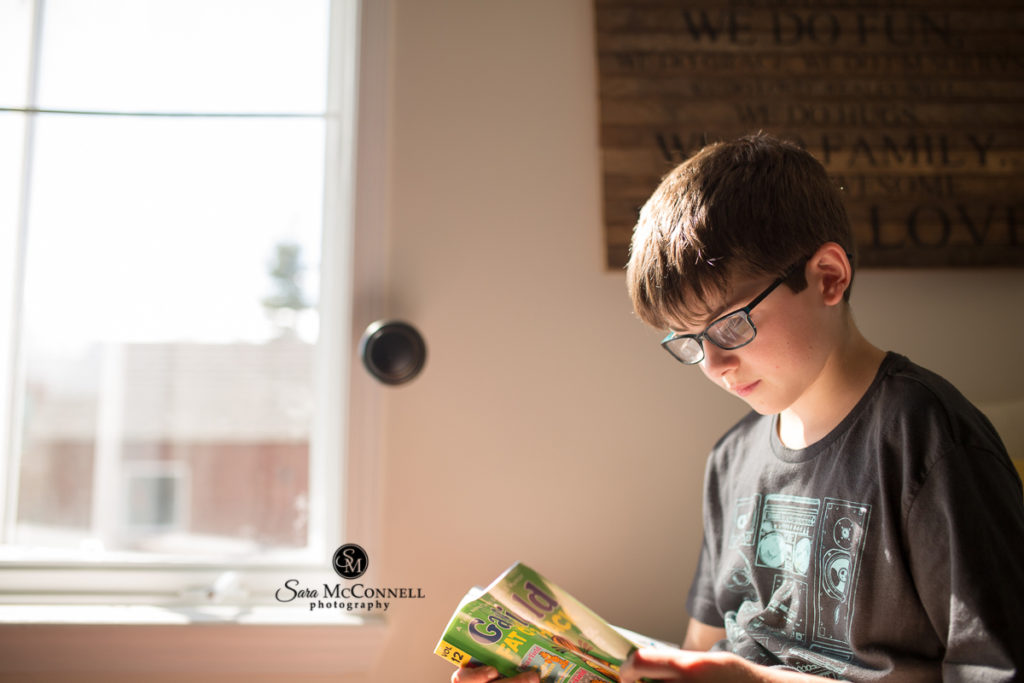 young boy reading a comic book