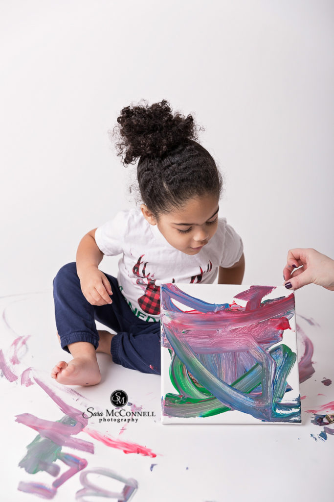 little girl looking at her painting