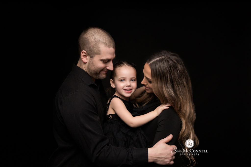 Mother and father with young child all wearing black clothing against black backdrop