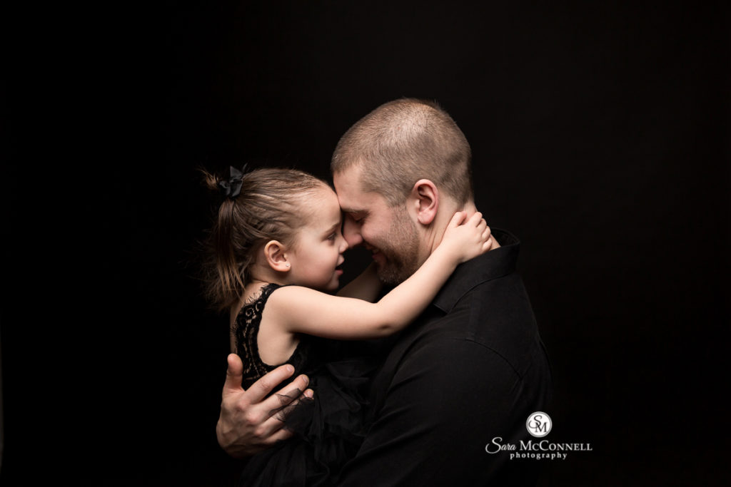 father and daughter touching foreheads