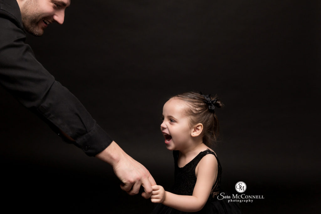 girl smiling holding her father's hand during family photos