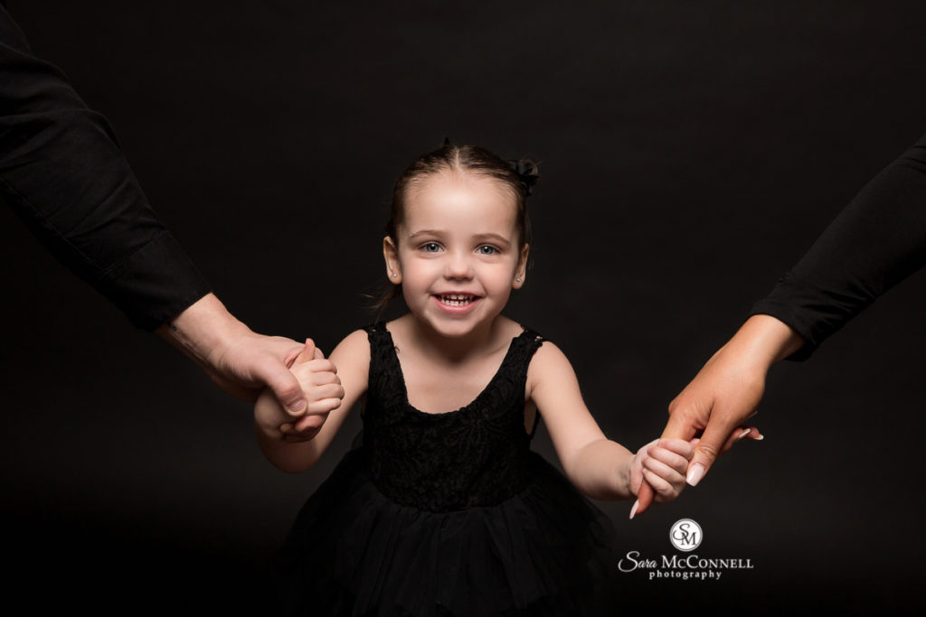 child smiling in black dress, holding her parents' hands during photo session