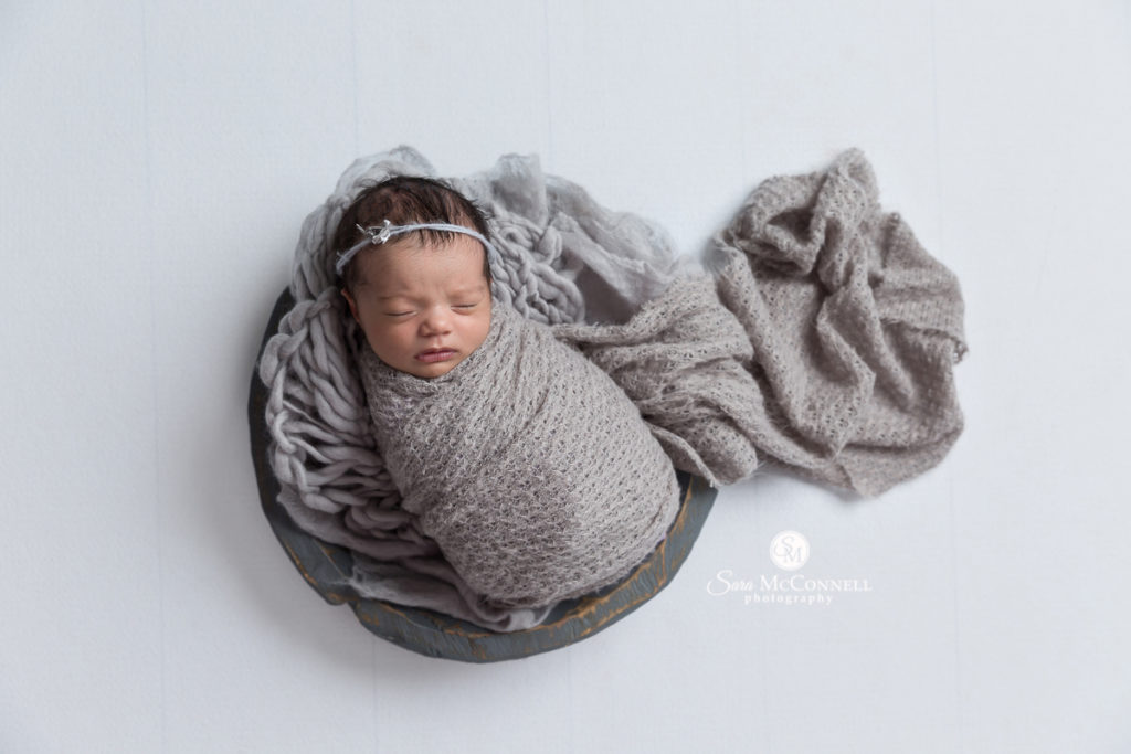 newborn baby wrapped in grey in a wooden grey bowl