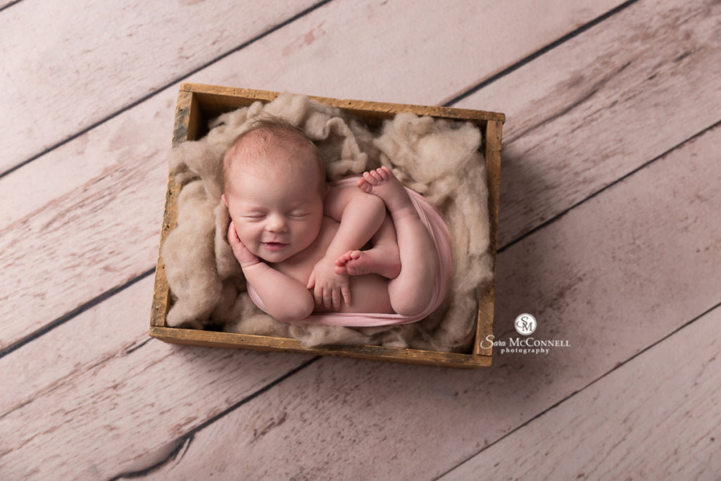 newborn baby sleeping in a wooden basket