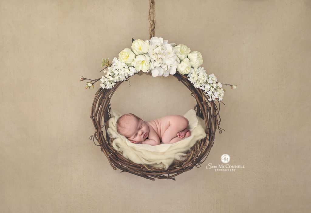 newborn baby in a grapevine wreath