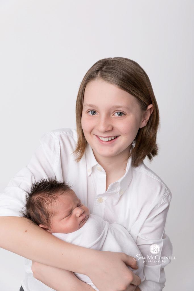 big sibling holding newborn baby