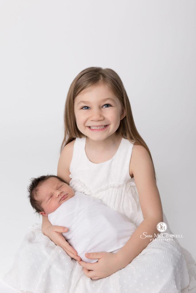 sister holding newborn baby