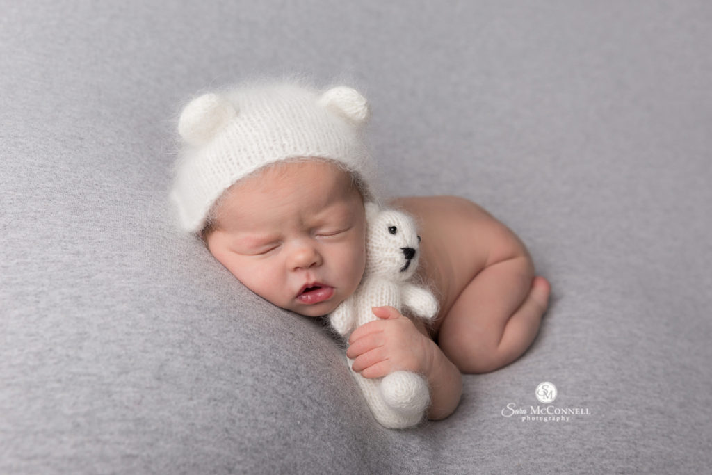 newborn baby sleeping with knitted bear