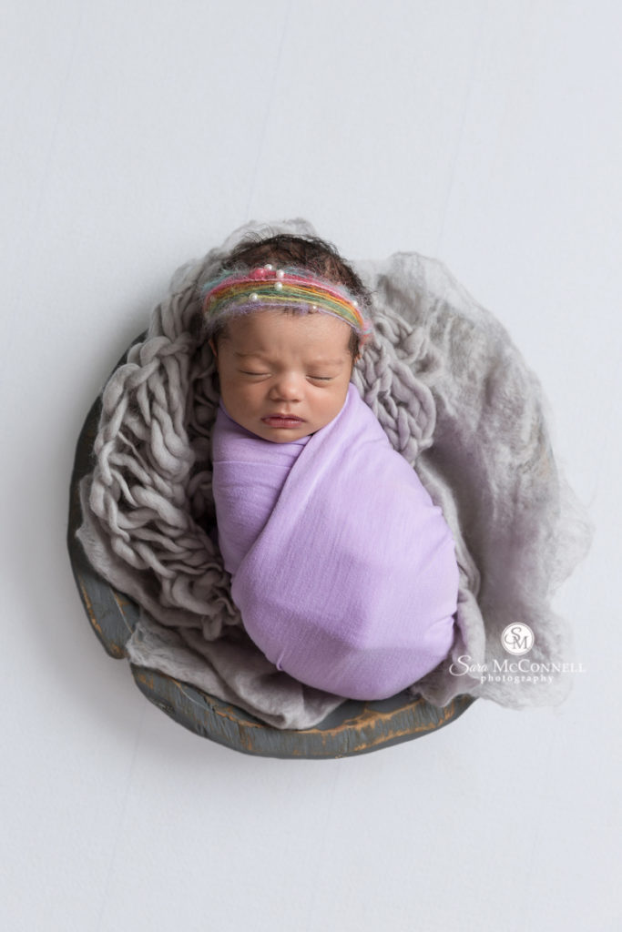 newborn baby wrapped in a purple blanket