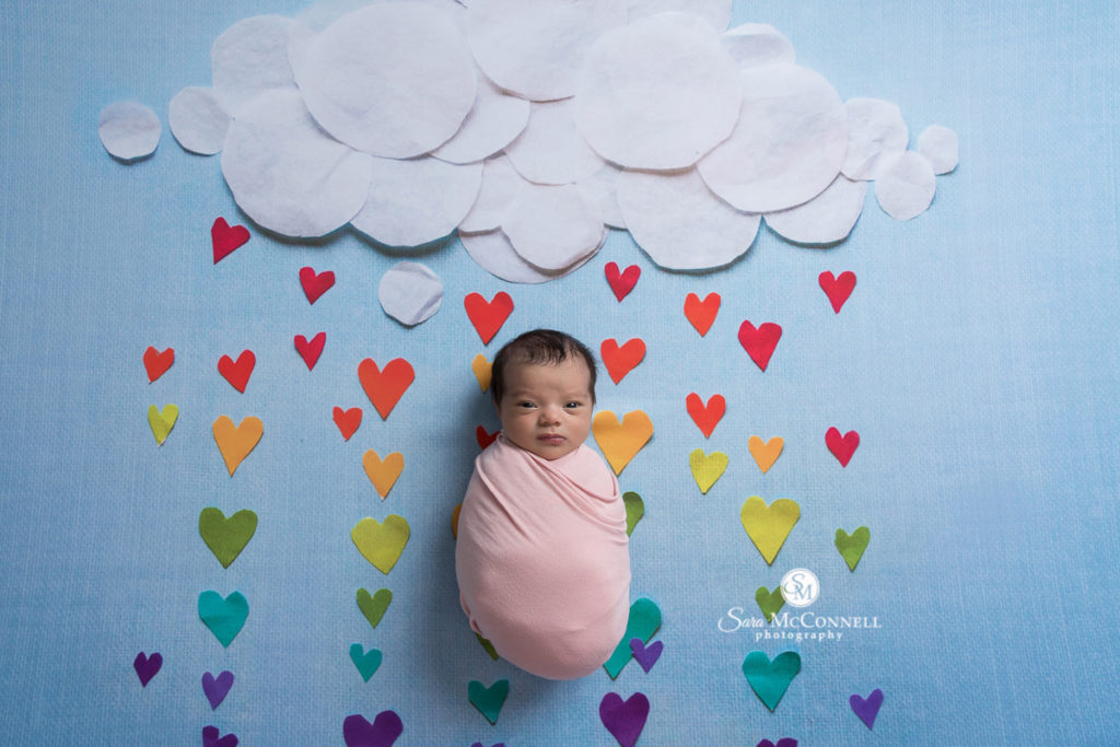 newborn baby with rainbow hearts in the background