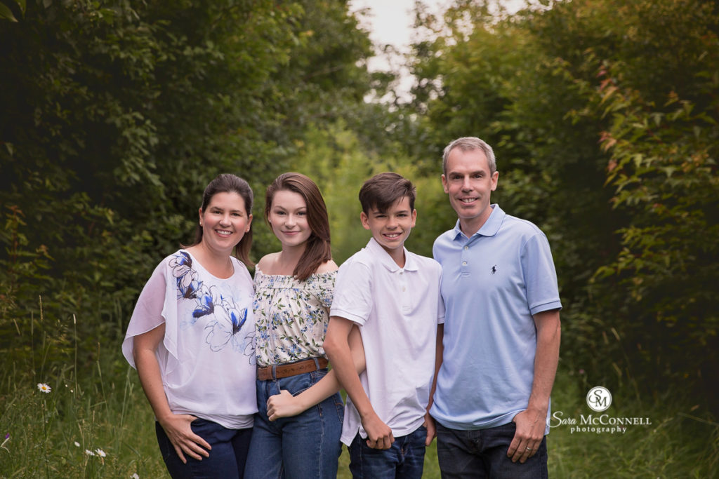 parents with preteen and teen children smiling outside for family photos