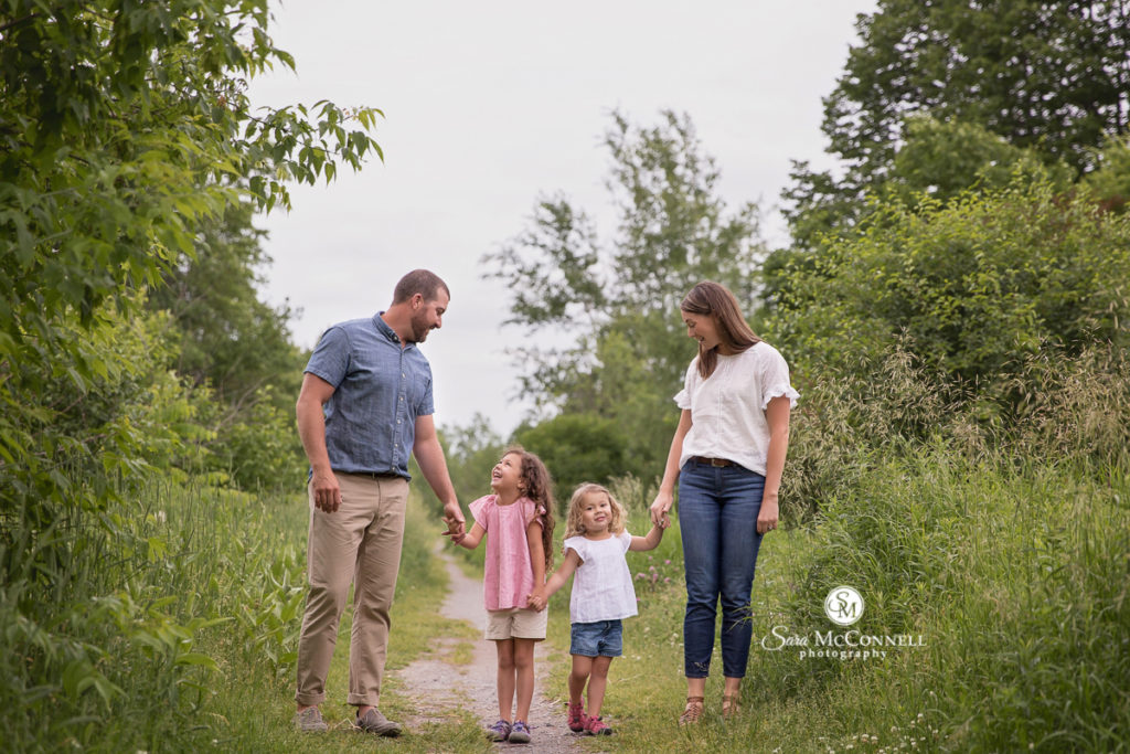 mom and dad holding their daughter's hands on a path in a field
