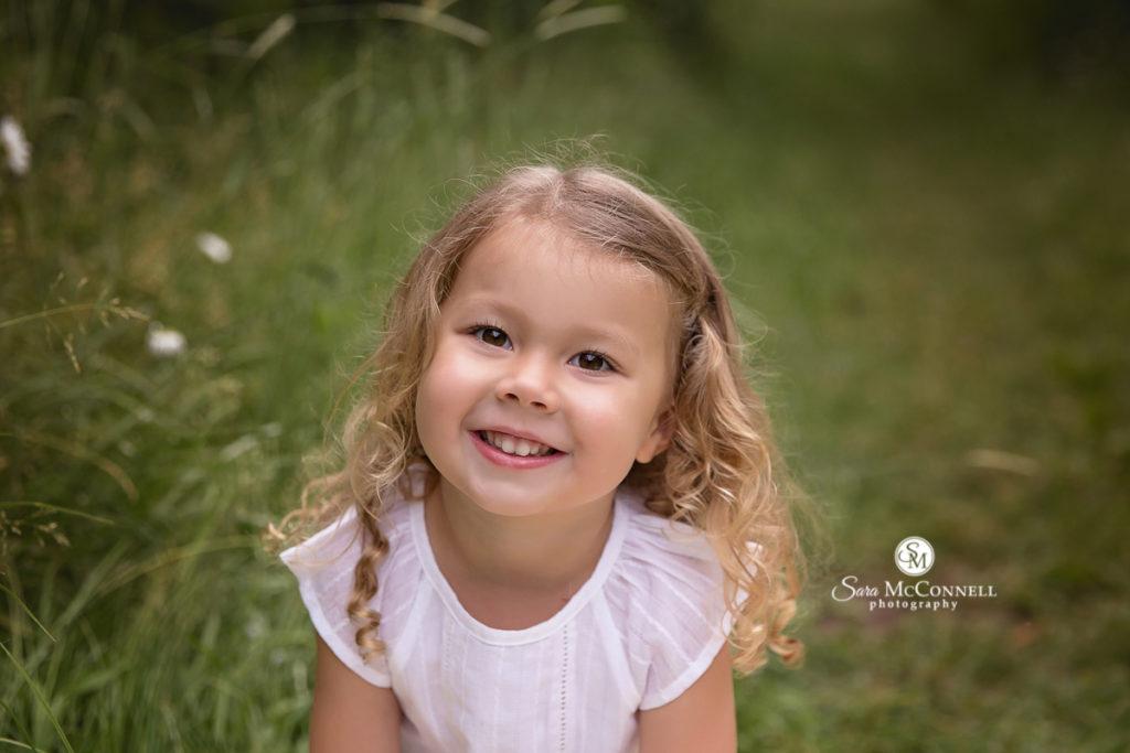 girl in white shirt smiling for family photos