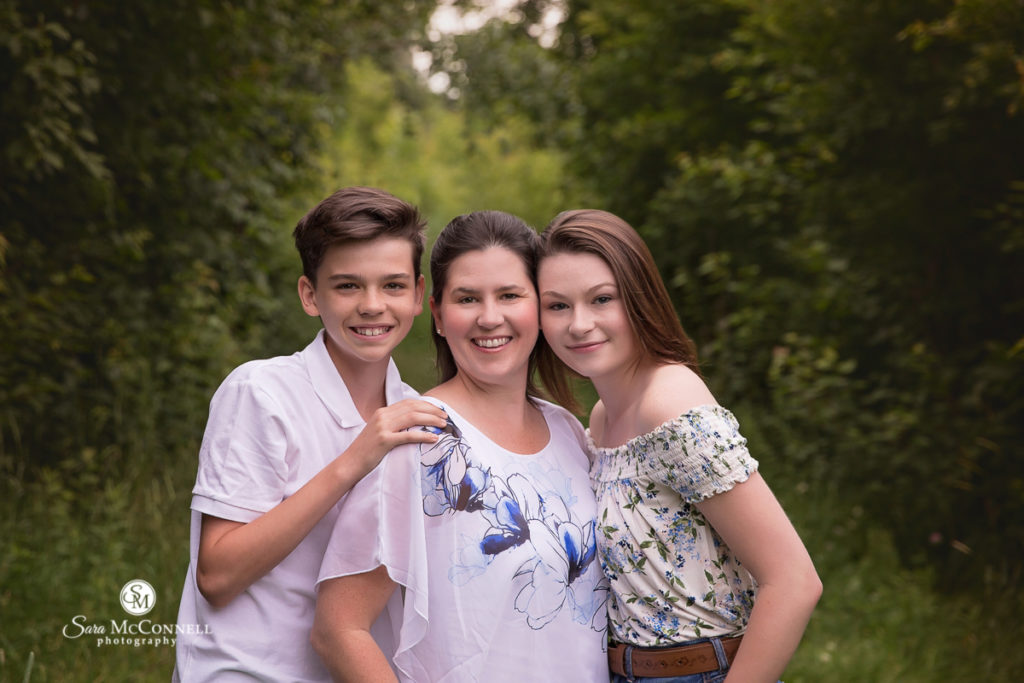 mother with her two children smiling outside