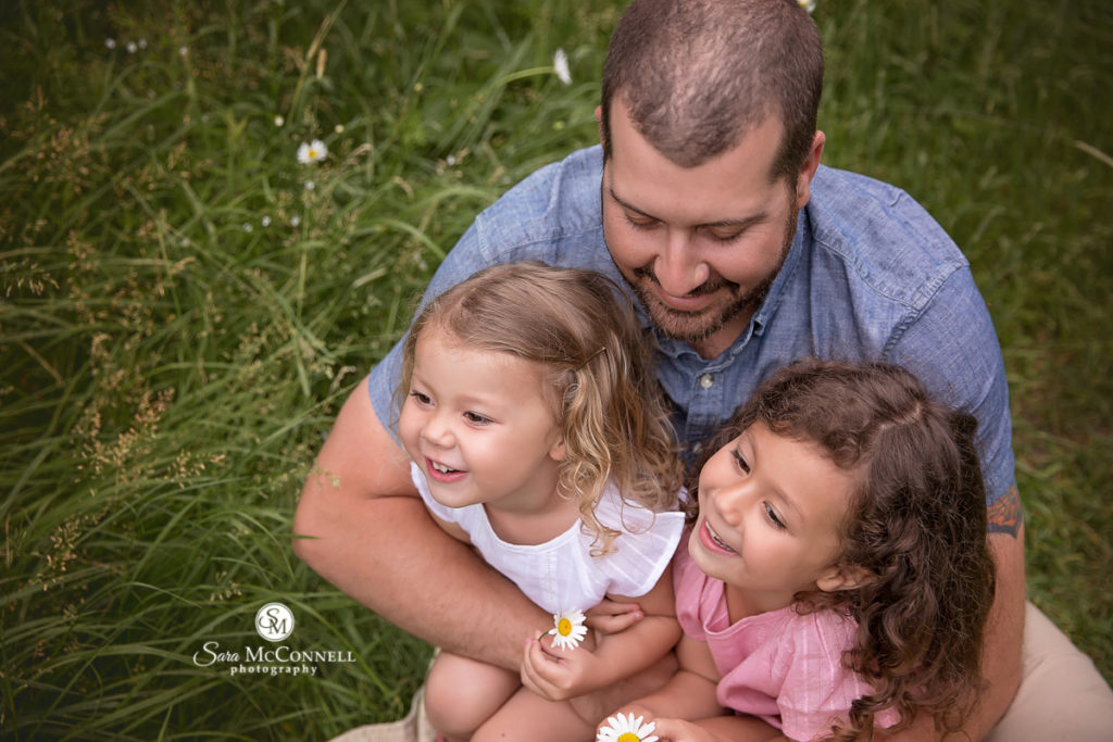 dad with his daughters in a field