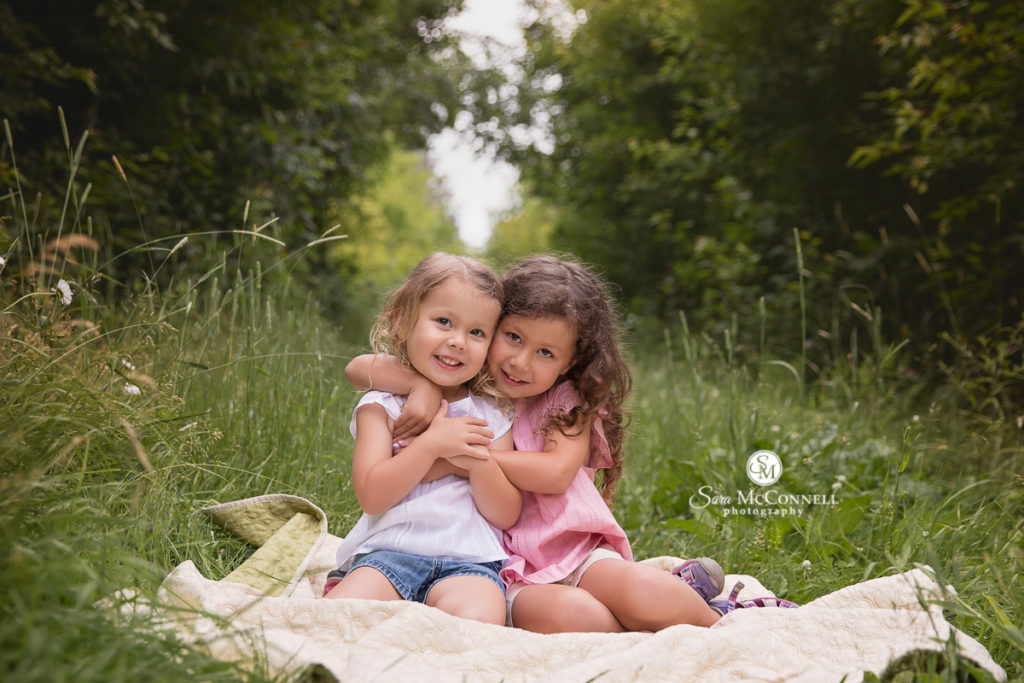 sisters hugging each other while on a blanket in a field