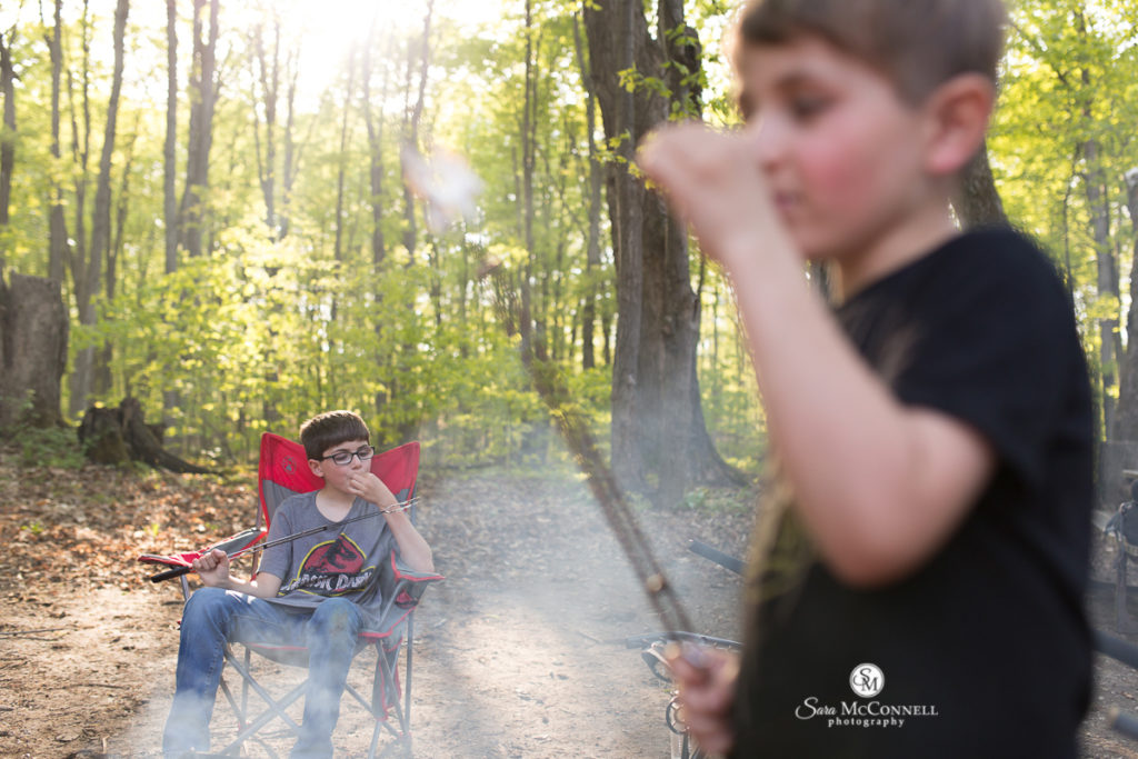 boys eating marshmallows around a camp fire