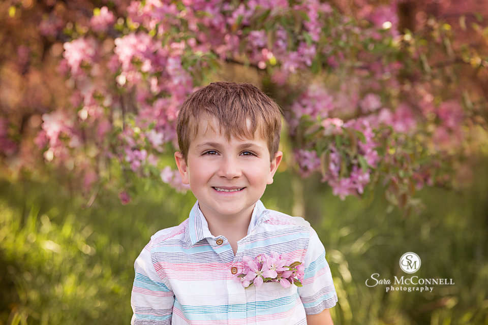 young boy having his photo taken among blossoms