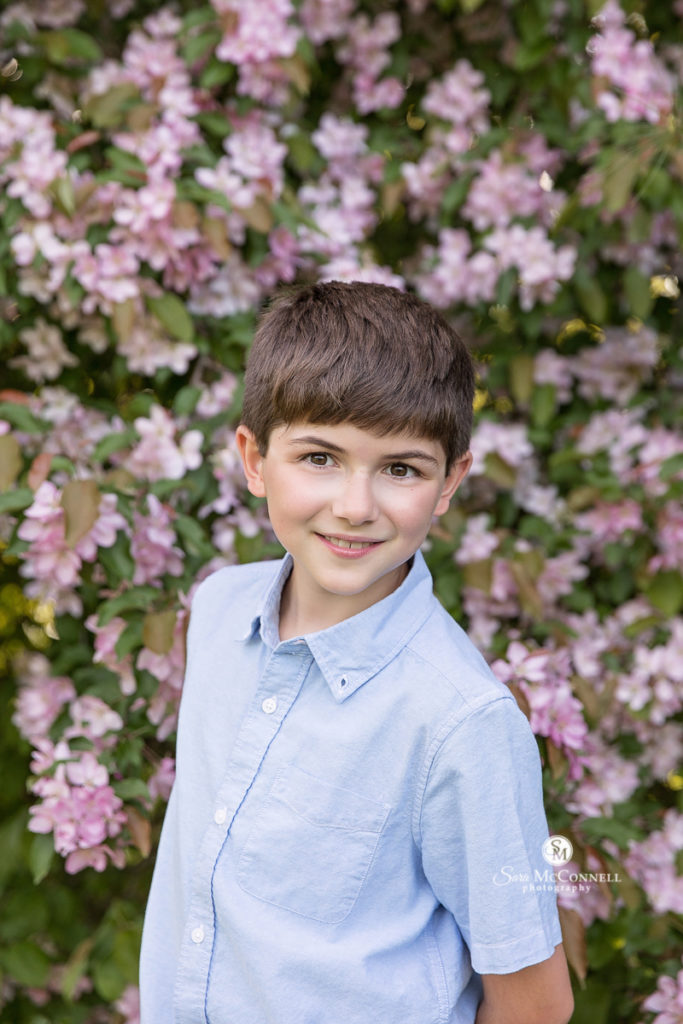photo of a boy in front of blossoms