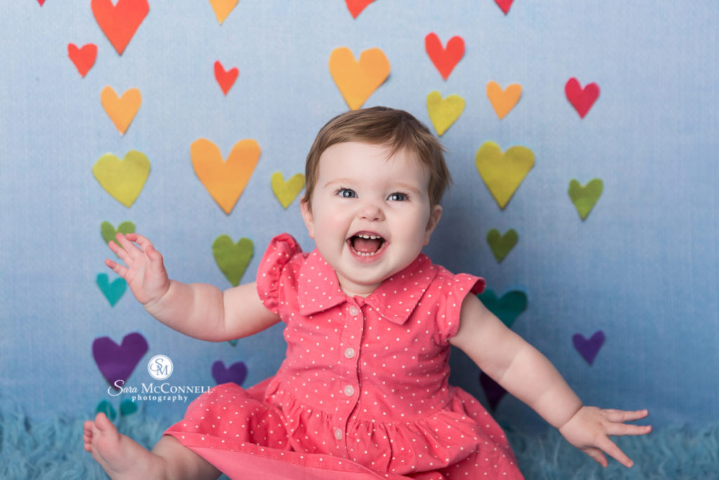 smiling baby in front of rainbow hearts