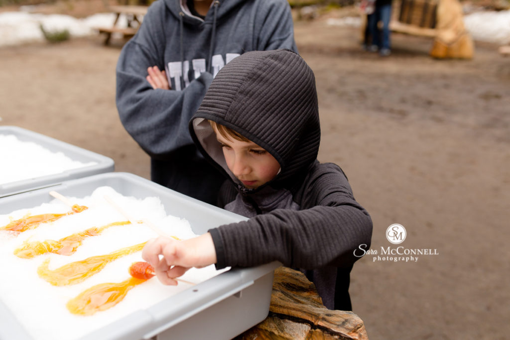 little boy making maple taffy at parc omega
