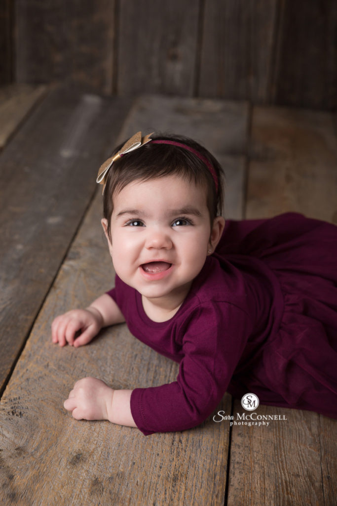 smiling 8 month old baby wearing a dark purple dress