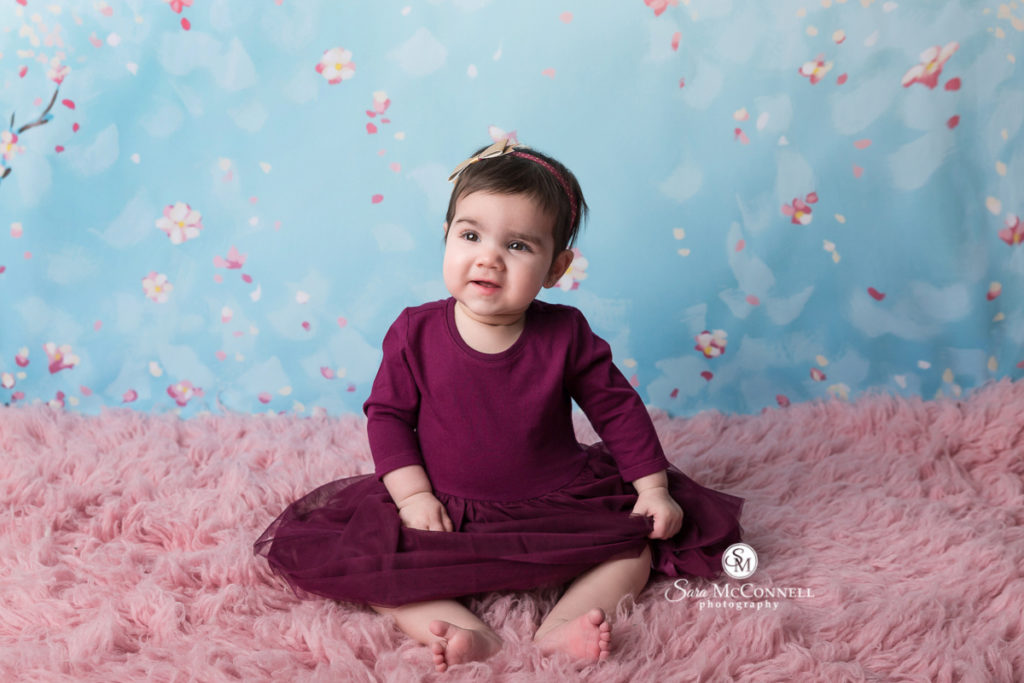 8 month old baby wearing a dark purple dress sitting on a pink rug
