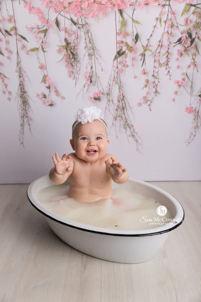 one year old in a milk bath in front of floral backdrop