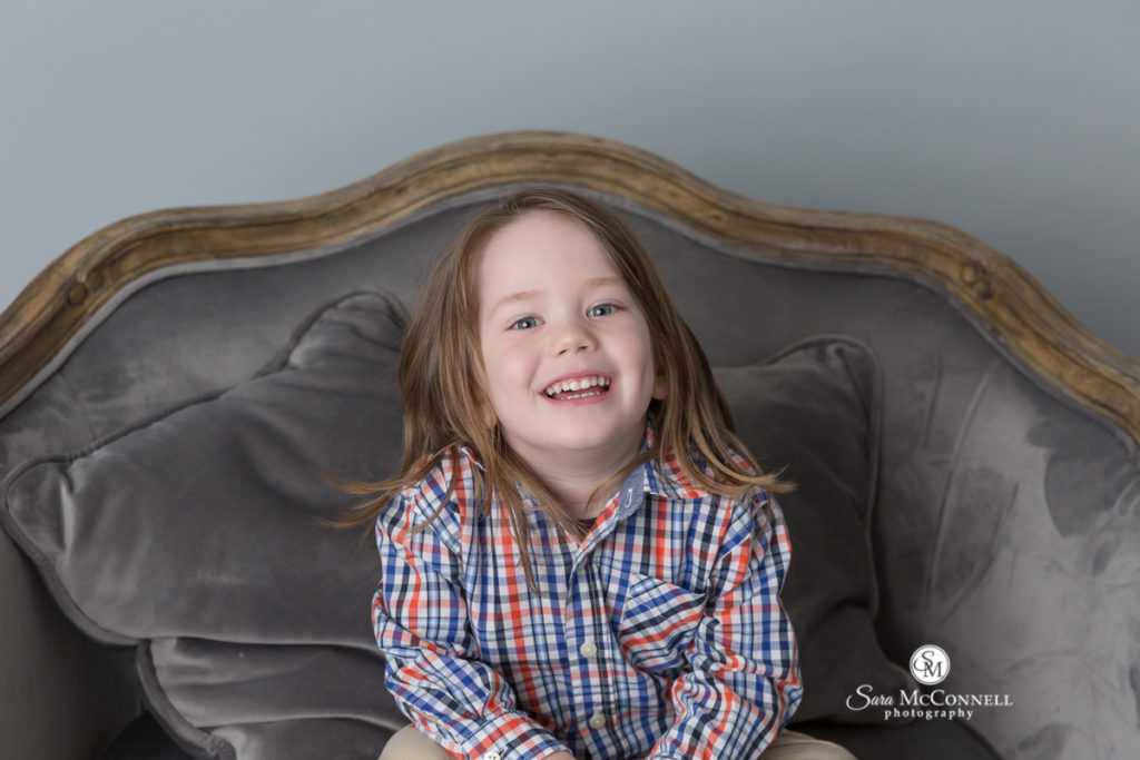 young child sitting on a grey couch