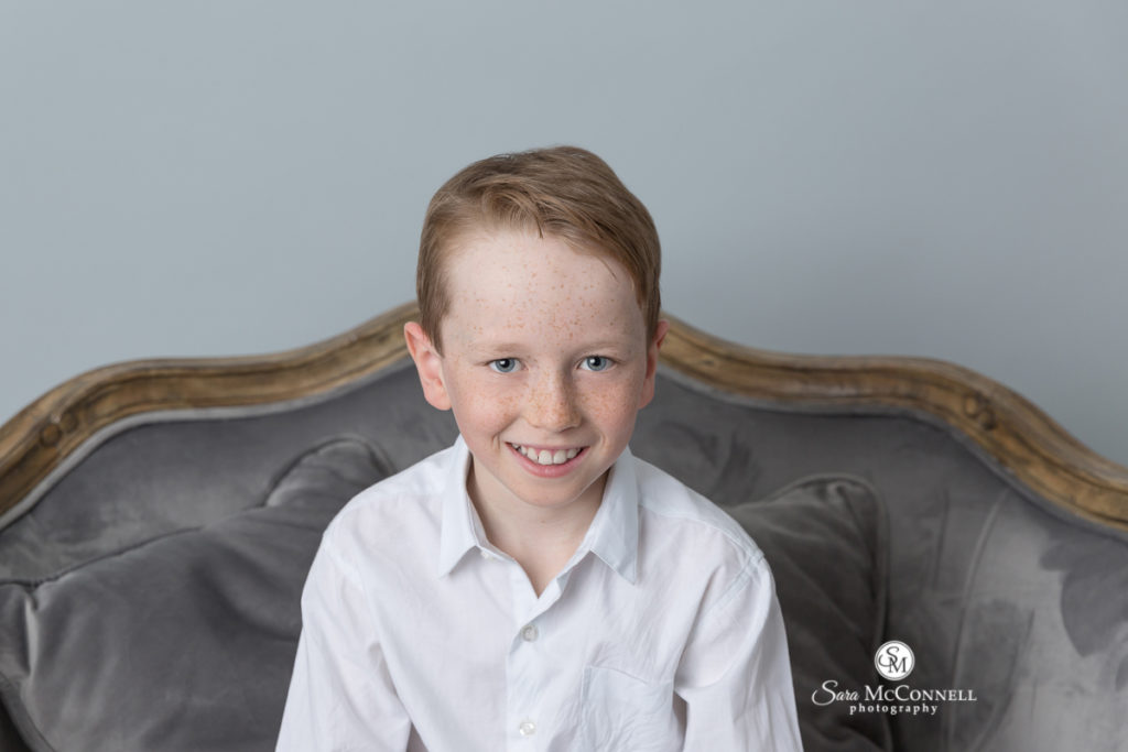 young child wearing a white shirt sitting on a grey couch