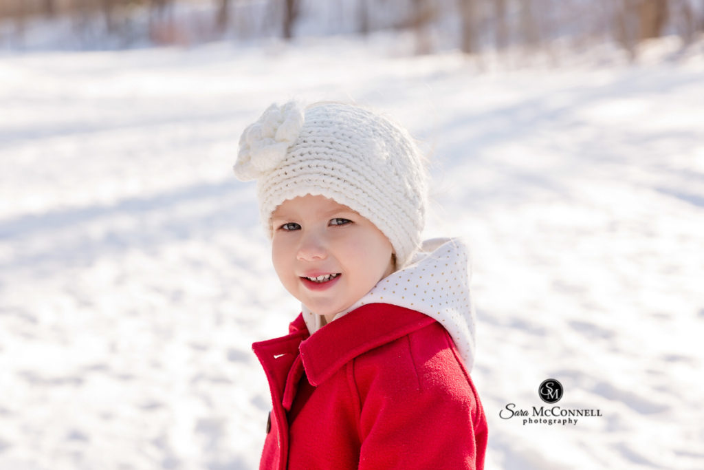 little girl wearing a red coat and white hat outside in the snow