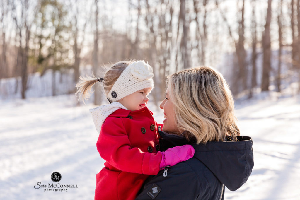 mother and daughter looking at each other in the snow