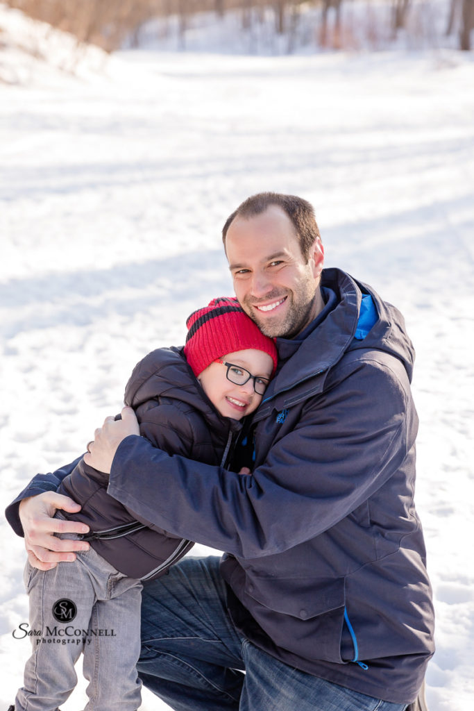 father and son hugging each other in the snow