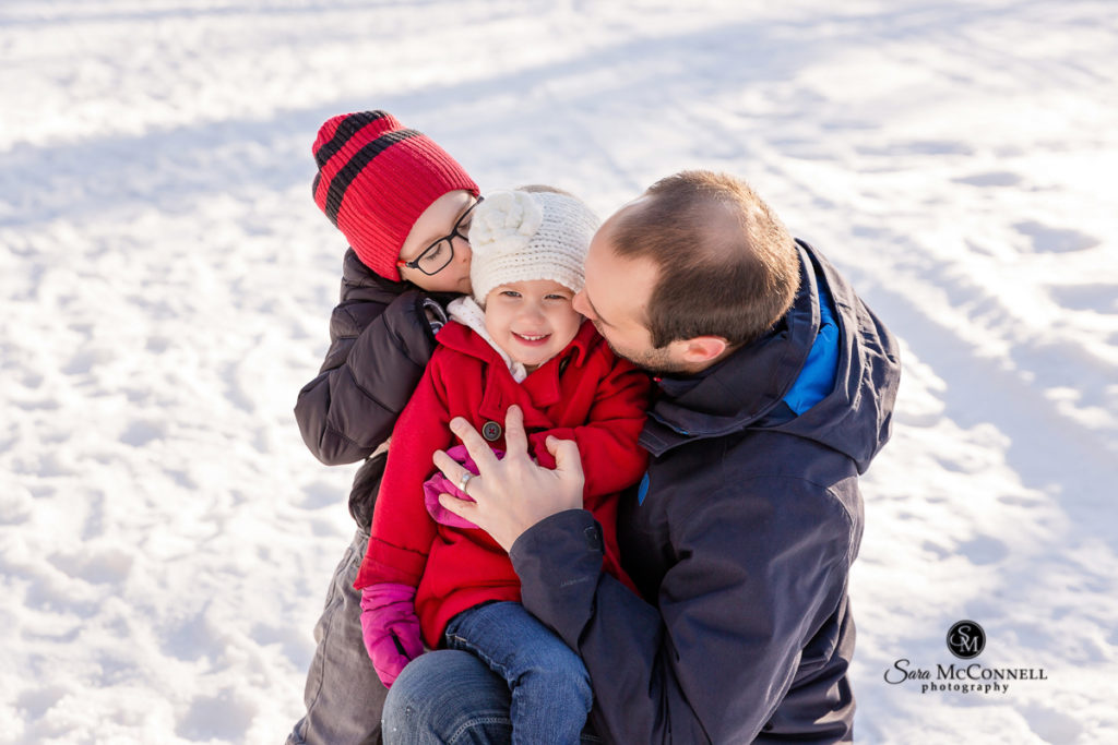 father and his two children hugging in the snow