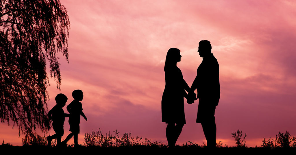 silhouette of parents with two children at sunset