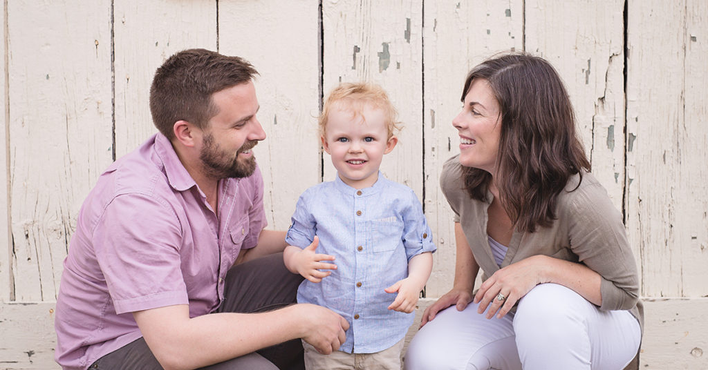 toddler in between parents smiling in front of wooden wall