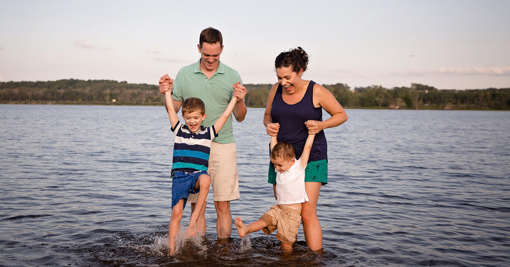 family of four splashing in the water during summer outdoor photo sessions with sara mcconnell