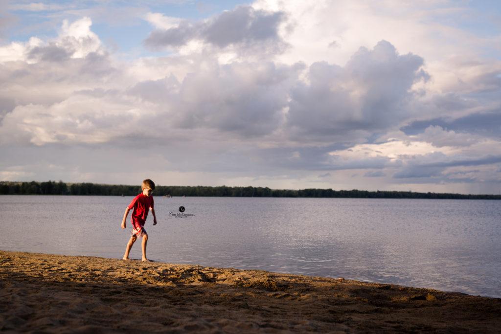 young boy walking along the beach