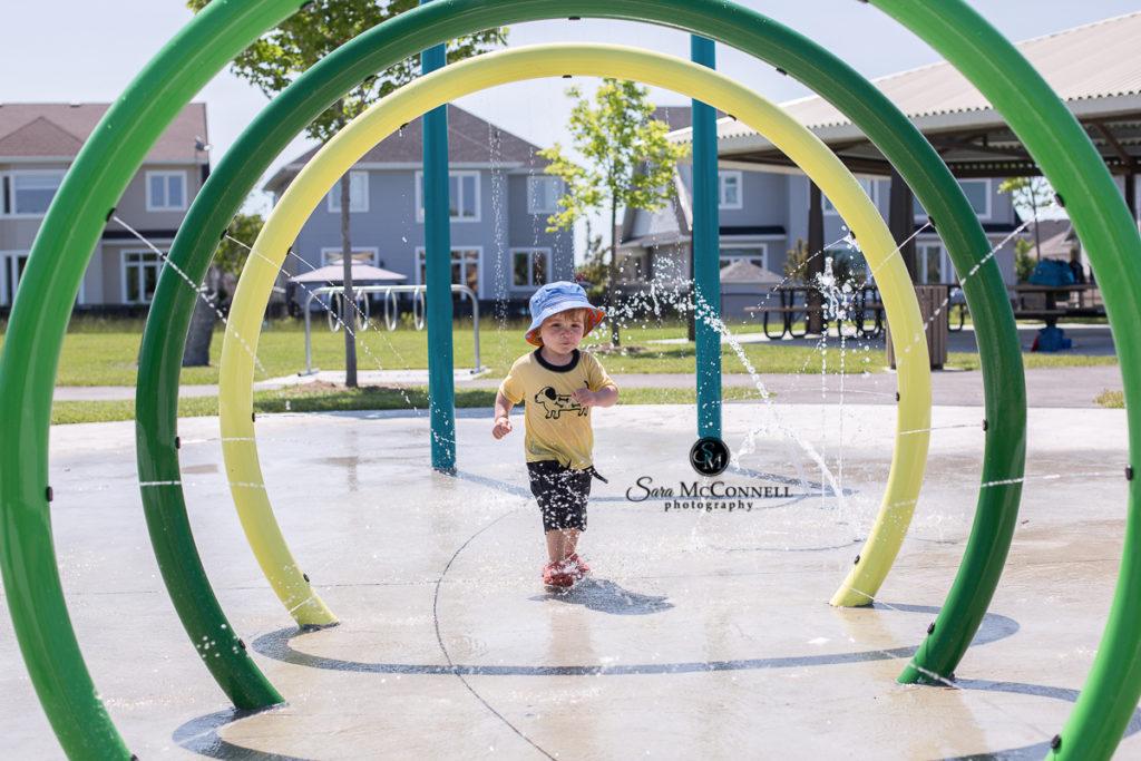 boy running through a splash park fountain in ottawa