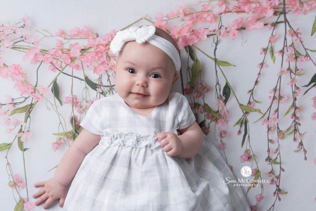 baby girl in a white dress and headband in front of flowers